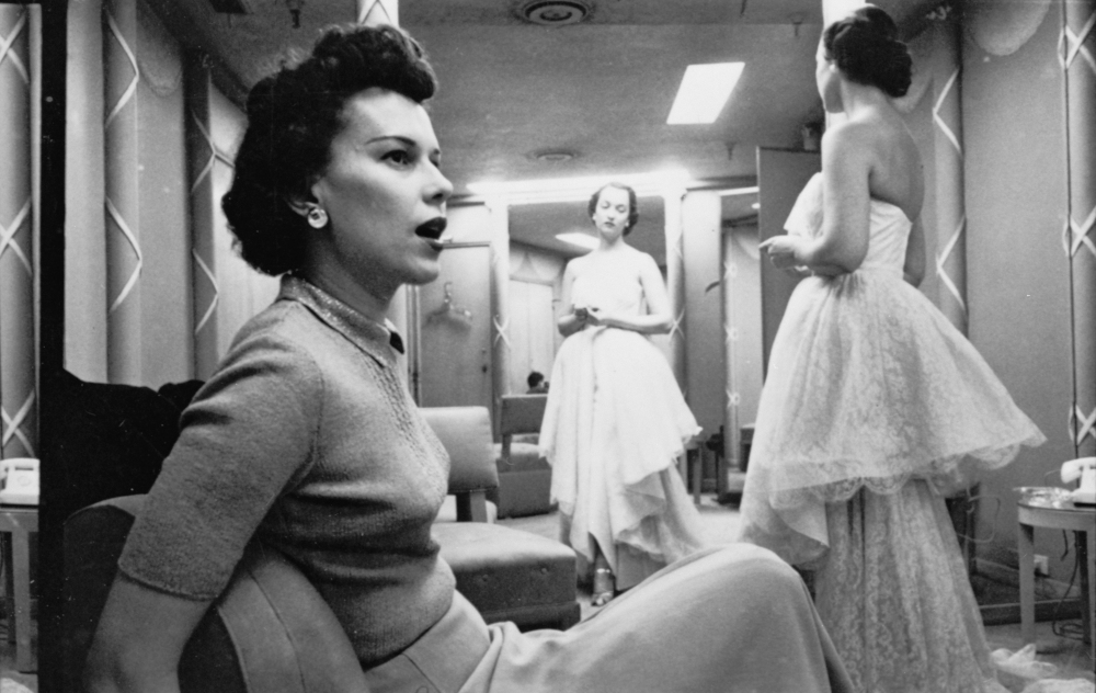 Stanley_Kubrick,_woman_seated_as_other_woman_models_clothes_cph.3d02343